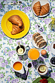 Breakfast with cooked eggs, cake, croissants, toast, tea and orange juice