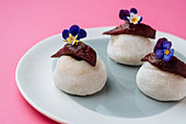 Rock shaped pastry with berry marmalade, flowers and placed on plate on pink background