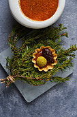 Fresh conifer twigs with pickled cone and boiled egg yolk, bowl with paprika