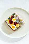 Fish sandwich with fresh vegetables and boiled quail eggs placed on plate