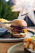Wildfleisch-Burger mit roten Zwiebeln, Käse, Tomaten, Salatblatt und Saucen