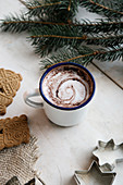 Cocoa in enamel mug, Spekulatius spiced biscuits and fir branch