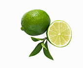 Whole lime and half a lime against a white background
