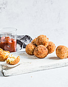 Arancini balls served with with tomato relish, on white wooden board