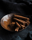 Cinnamon sticks and powder in a bowl, on a dark background
