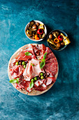 Cold cuts with olives and marinated vegetables in small bowls