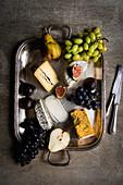 Käseauswahl serviert mit Früchten auf Silbertablett
