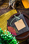 Place setting with a card and leaf decorations on a rustic wooden table
