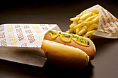 Street vendor hot dog with mustard, pickle relish and a bag of french fries