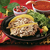 Pork carnitas in a crispy corn taco shell garnished with tomatillo, peppers, shredded lettuce and tomato salsa
