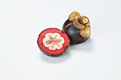 Mangosteen, whole and halved on a white background