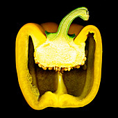 A sliced yellow pepper against a black background