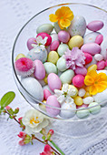 Glass bowl with Easter eggs and flowers