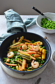 Colorful pasta with shrimps and green peas in a white wine sauce