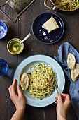Spaghetti with garlic, parsley, chilli, olive oil and parmesan, bread, permesan cheese, olive oil, water in a glass, salt