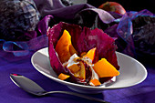 Pumpkin and plum dessert on a red cabbage leaf
