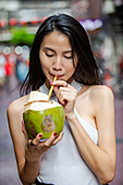 Young Asian woman drinks fresh coconut water from a coconut