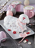 Baked Easter lamb bread with white icing decorated with sugar flowers