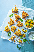 Indian deep fried onion bhajis (vegan) with mango relish and coconut mint dip