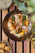 Fried eggs with shrimps covered by herbs in pan on wooden table