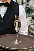 Waiter holding tray with glass of white wine during party
