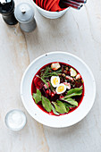 Palatable red beetroot soup with boiled eggs and herbs in