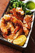 Baked big shrimps in square plate with lemon fresh parsley and green sauce