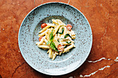 Pasta with pieces of cherry tomatoes and greenery