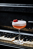 Red alcohol cocktail with white foam decorated with fresh raspberry on piano keys