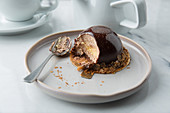 Creamy mousse in chocolate decorated with cereals on plate with spoon