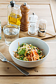 Tasty salad with soybean sprout and seeds in a bowl on wooden table