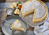 Veganer Apfelstrudel-Cheesecake auf Kuchenständer mit abgeschnittem Stück auf Teller