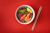 Asian stir fry soba noodles with shrimps, vegetables, green peas, red pepper