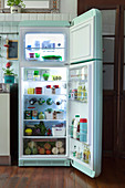 A view into an open, mint-green retro fridge filled with food
