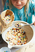 Girl mixing cereals and sweets