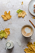 Cappuccino mit Milchschaumherz umgeben von Herbstblättern