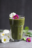 Green smoothie with edible flowers