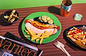 Pommes, Baked Beans und Essiggurken auf Telller mit Hot-Dog-Motiv
