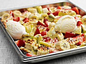 Oven-baked fruit on a baking sheet served with vanilla ice cream