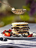 Powdered sugar dusted on a pancake stack with berries and cream