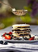 Puderzucker riesel auf Pancake-Stapel mit Beeren und Sahne