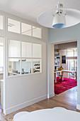 Küche abgetrennt vom Ess- und Wohnzimmer durch weiße Wand mit eingesetztem Sprossenfenster