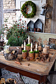 Ländliche Adventsdekoration mit Kerzen in Blechdosen und Gesteck aus Zweigen