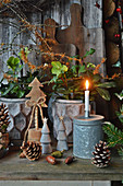 Christrosen mit Zweigen von Zaubernuss, Holzbäumchen, Zapfen und Kerze