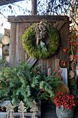 Weihnachtliche Dekoration mit Mooskranz, Kasten mit Zweigen und Hagebutten