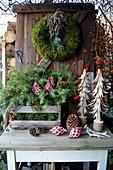 Weihnachtliche Dekoration mit Mooskranz, Kasten mit Zweigen, Holzbäumchen und Hagebutten