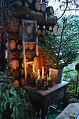 Kleine Adventsdekoration mit Fichte und altem Fensterrahmen am Brennholzstapel
