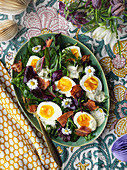 A mixed leaf salad with hard-boiled eggs, bacon and daisies