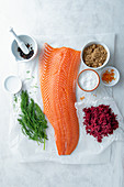 Fillet of salmon and ingredients for beetroot, juniper and gin cured salmon (gravlax)