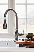 A vintage-style kitchen tap with an extendable hose